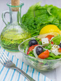 Greek salad in a glass bowl. On wooden table Royalty Free Stock Photos