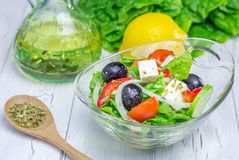 Greek salad in a glass bowl. On wooden table Royalty Free Stock Images