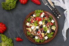 Greek salad is located on a plate on a dark background royalty free stock photos