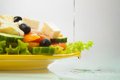 Greek Salad with oil flowing. On a white background with oil flowing Royalty Free Stock Photos