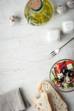 Greek salad  with olive oil , fork and bread Royalty Free Stock Photography