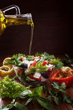 Greek salad with olive oil pouring from a bottle. Greek salad with olive oil pouring from a bottle and fresh vegetables stock photos
