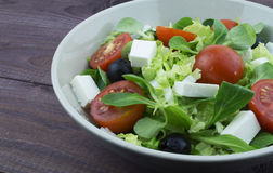 Greek salad with olives, tomatoes, feta cheese. In a plate on a dark wooden background Stock Images