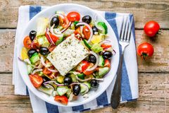 Greek salad of organic tomatoes, cucumber, red onion, olives and feta cheese. Greek salad of organic vegetables with tomatoes, cucumber, red onion, olives and stock images