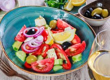 Greek salad of organic vegetables with tomatoes, cucumbers, red onion, olives, feta cheese and glass of wine on wooden background Royalty Free Stock Image