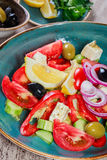 Greek salad of organic vegetables with tomatoes, cucumbers, red onion, olives, feta cheese and glass of wine on wooden background Royalty Free Stock Photography