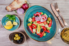 Greek salad of organic vegetables with tomatoes, cucumbers, red onion, olives, feta cheese and glass of wine on wooden background. Royalty Free Stock Photos