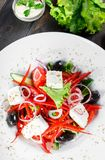 Greek salad of organic vegetables with tomatoes, cucumbers, red onion, olives, feta cheese and sweet pepper on wooden background. Healthy food. Top view stock photo