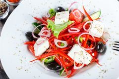 Greek salad of organic vegetables with tomatoes, cucumbers, red onion, olives, feta cheese and sweet pepper on wooden background. Healthy food. Top view stock photos
