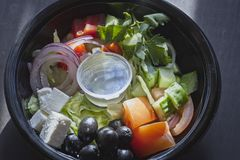 Greek salad in the package. Open package with Greek salad on the table Royalty Free Stock Photos