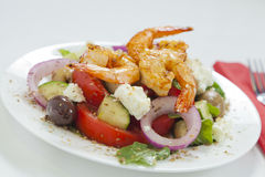 Greek salad with piri piri shrimps. Traditional Greek salad with spicy chili prawns on a white plate Royalty Free Stock Images
