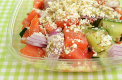 Greek salad to go. Greek salad in plastic container on green checkered tablecloth Stock Photo