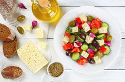 Greek salad on plate, ingredients on paper Stock Photography