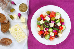 Greek salad on plate, ingredients on paper Stock Photos