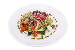 Greek salad in plate. Isolated on white background Stock Image