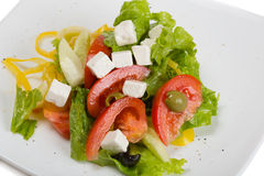 Greek salad in plate isolated on white Stock Photo