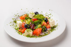 Greek salad in a plate. On a white background Royalty Free Stock Photo