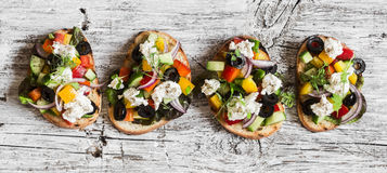 Greek salad style bruschetta on a wooden rustic board, top view. Delicious appetizers Stock Photos