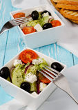 Greek salad. In a stylish white bowls on the blue table Stock Photography