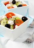 Greek salad. In a stylish white bowls on the blue table Royalty Free Stock Photography