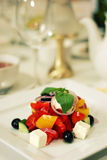 Greek salad with tomato olives on plate. Healthy green salad on white plate in luxury restaurabt royalty free stock photo
