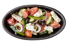 Greek Salad Top View Isolated. Greek salad in rustic black bowl, top view, isolated on white Royalty Free Stock Photo