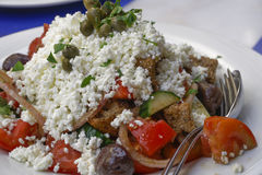 Greek salad with trimmed white cheese closeup served on white di Stock Images