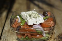 A greek salad with vegetable tomatoes onions black olives, is the classic cheese of feta name the Greek goat cheese royalty free stock images