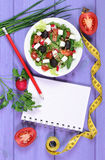 Greek salad with vegetables, centimeter and notepad for notes, healthy food and slimming concept. Greek salad with vegetables, tape measure and notepad for Stock Photos