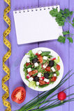 Greek salad with vegetables, centimeter and notepad for notes, healthy food and slimming concept. Greek salad with vegetables, tape measure and notepad for Stock Photo
