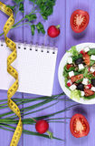 Greek salad with vegetables, centimeter and notepad for notes, healthy food and slimming concept. Greek salad with vegetables, tape measure and notepad for Royalty Free Stock Photography