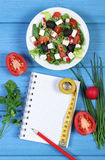 Greek salad with vegetables, centimeter and notepad for notes, healthy food and slimming concept. Greek salad with vegetables, tape measure and notepad for Stock Image