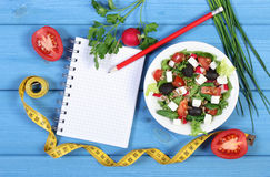 Greek salad with vegetables, centimeter and notepad for notes, healthy food and slimming concept. Greek salad with vegetables, tape measure and notepad for Royalty Free Stock Photos