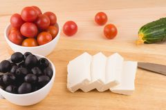 Greek salad with vegetables, feta cheese, black olives in proces. S. Wooden background . Top view Stock Image