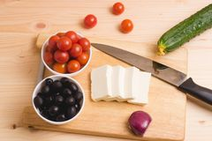Greek salad with vegetables, feta cheese, black olives in proces. S. Wooden background . Top view Stock Images