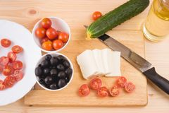 Greek salad with vegetables, feta cheese, black olives in proces. S. Wooden background . Top view Royalty Free Stock Photo