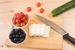 Greek salad with vegetables, feta cheese, black olives in proces. S. Wooden background . Top view Stock Photos