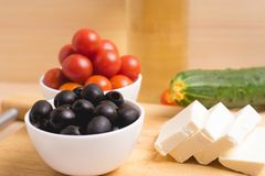 Greek salad with vegetables, feta cheese, black olives in proces. S. Wooden background . Top view Stock Photo
