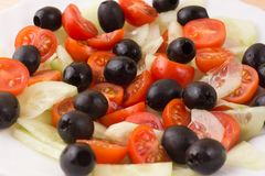 Greek salad with vegetables, feta cheese, black olives in proces. S. Wooden background . Top view Stock Photography