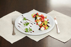 Greek salad with vegetables, feta cheese and black olives. On white plate Stock Images