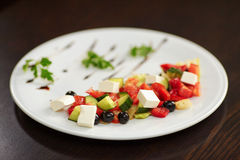 Greek salad with vegetables, feta cheese and black olives. On white plate. Selective focus Stock Image