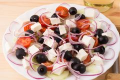 Greek salad with vegetables, feta cheese, onion and black olives. On a wooden background . Top view Royalty Free Stock Images