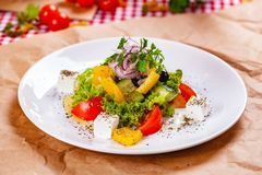 Greek salad with vegetables and feta cheese on white plate. Close up stock photos
