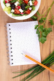 Greek salad with vegetables and notepad for notes, healthy nutrition. Fresh greek salad with vegetables and notepad for notes, concept of healthy nutrition Royalty Free Stock Photography
