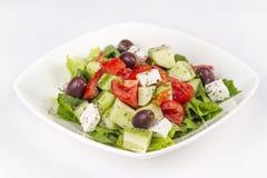 Greek salad on a white background. Greek salad in plate on a white background stock images