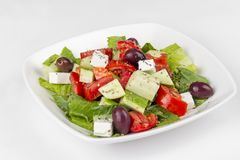 Greek salad on a white background. In plate Stock Images