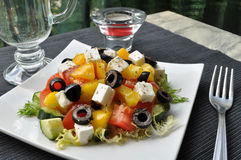 Greek salad on white dish. On black background Royalty Free Stock Images
