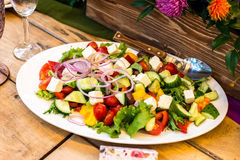 Greek salad on a white oval plate stock image