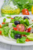 Greek salad on a white plate. Closeup Royalty Free Stock Images
