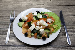 Greek salad on a white plate with fork and knife on a wooden table. Can be used as a photo for restaurant menus, bistro. European, Stock Photos